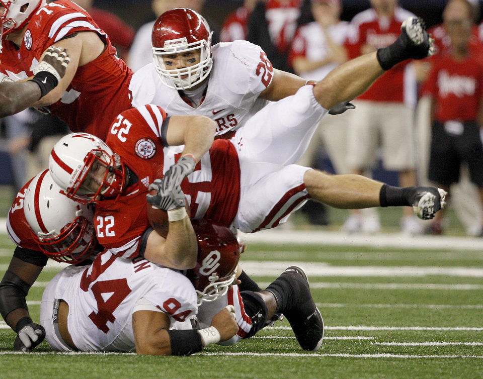 Photo - OU's Pryce Macon brings down Nebraska's Rex Burkhead as Travis Lewis watches during the Big 12 football championship game between the University of Oklahoma Sooners (OU) and the University of Nebraska Cornhuskers (NU) at Cowboys Stadium on Saturday, Dec. 4, 2010, in Arlington, Texas.  Photo by Bryan Terry, The Oklahoman