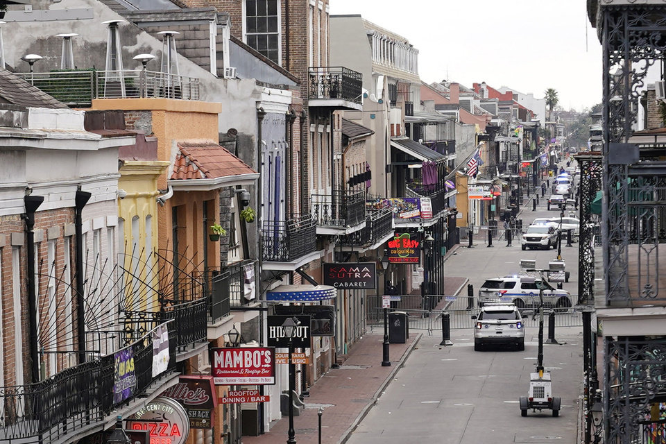 Photo -  Bourbon Street, which is normally packed with revelers, is seen deserted during Mardi Gras in the French Quarter of New Orleans, Tuesday, Feb. 16, 2021. Coronavirus-related limits on access to Bourbon Street, shuttered bars and frigid weather all prevented what New Orleans usually craves at the end of Mardi Gras season — streets and businesses jam-packed with revelers. (AP Photo/Gerald Herbert)
