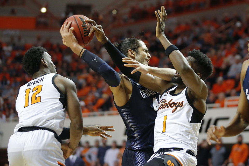 Photo - Georgetown's Omer Yurtseven (44) reaches for the ball between Oklahoma State's Cameron McGriff (12) and Jonathan Laurent (1) during a college basketball game between the Oklahoma State University Cowboys (OSU) and the Georgetown Hoyas at Gallagher-Iba Arena in Stillwater, Okla., Wednesday, Dec. 4, 2019. Georgetown won 84-71. [Bryan Terry/The Oklahoman]