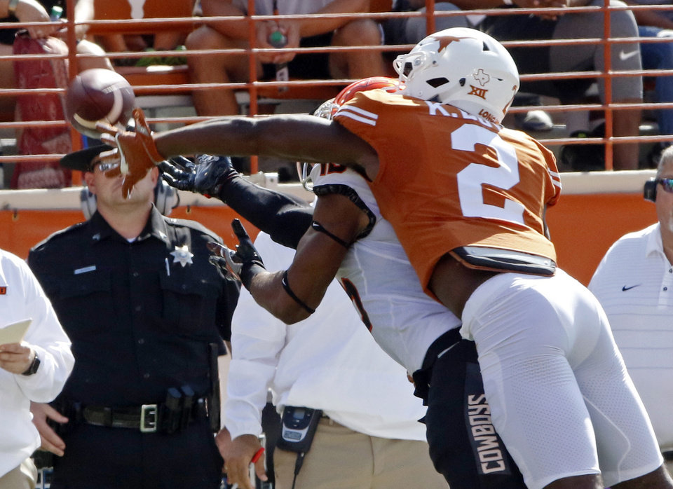 Photo - Texas defensive back Kris Boyd (2) breaks up a pass intended for Oklahoma State's Chris Lacy during the first half of an NCAA college football game, Saturday, Oct. 21, 2017, in Austin, Texas. (AP Photo/Michael Thomas)