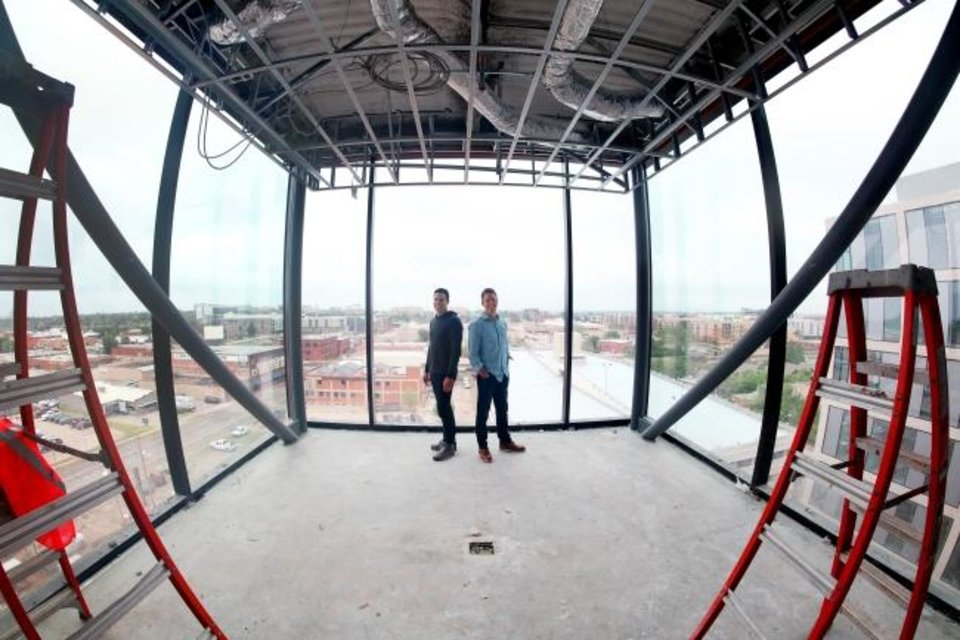 Photo -  David Burnett, left, and Andy Burnett pause in the sixth floor conference room that extends outside of the future Heartland headquarters at NW 5 and Broadway. [DOUG HOKE/THE OKLAHOMAN]