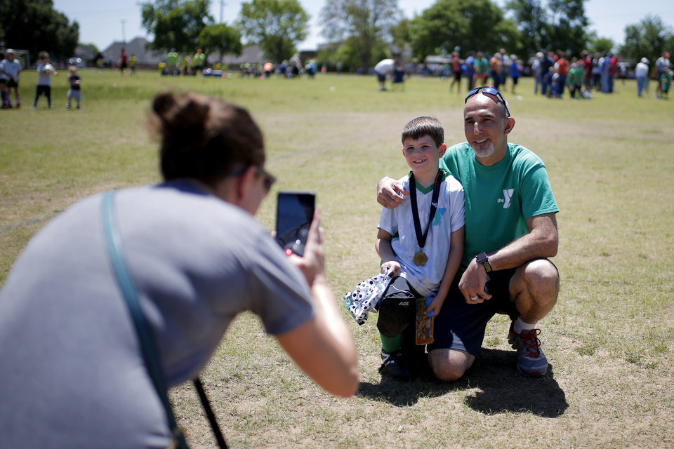 Photo -  Rebecca Smith takes a photo of her son, Wyatt Smith, 8, and his soccer coach, Estabraq Al-Adhami, after the team's last game of the season in Oklahoma City. [Photo by Bryan Terry, The Oklahoman]