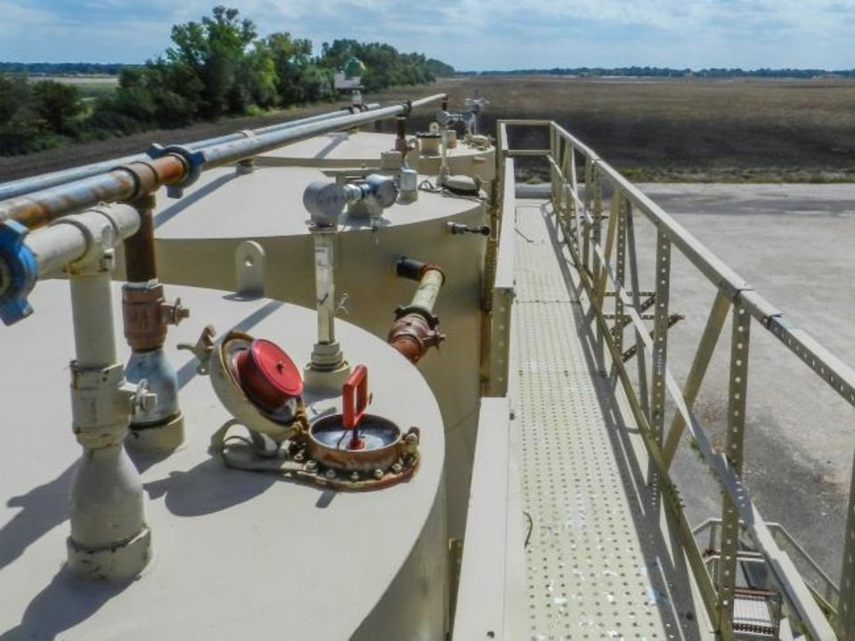 Photo -  A HARP is mounted in an open thief hatch on one of several production tanks at a Chesapeake Energy location in Oklahoma. The device makes it possible to inspect and repair hatch lids and rims on the tanks without exposing workers to harmful emissions. [PHOTO PROVIDED BY CHESAPEAKE ENERGY]
