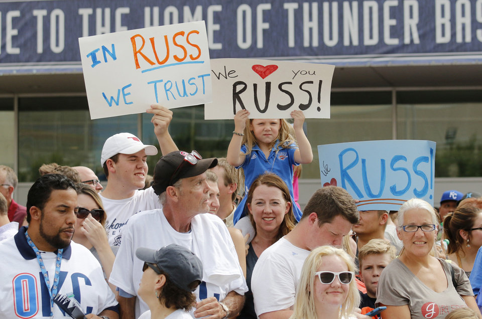 Photo - Rose Holland, 4, pokes out between signs waiting to see Russell Westbrook returns to sign an extension of his contract and is greeted by hundreds of Thunder fans outside of the Chesapeake Arena, Thursday, August 4, 2016. Photo by Doug Hoke, The Oklahoman