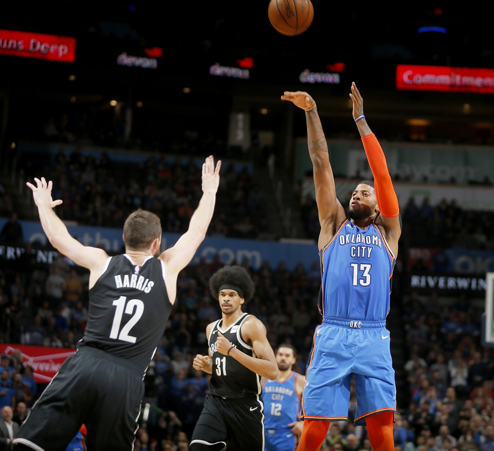 Photo - Oklahoma City's Paul George (13) shoots over Brooklyn's Joe Harris (12) during an NBA basketball game between the Oklahoma City Thunder and the Brooklyn Nets at Chesapeake Energy Arena in Oklahoma City, Wednesday, March 13, 2019. Oklahoma City won 108-96. Photo by Bryan Terry, The Oklahoman