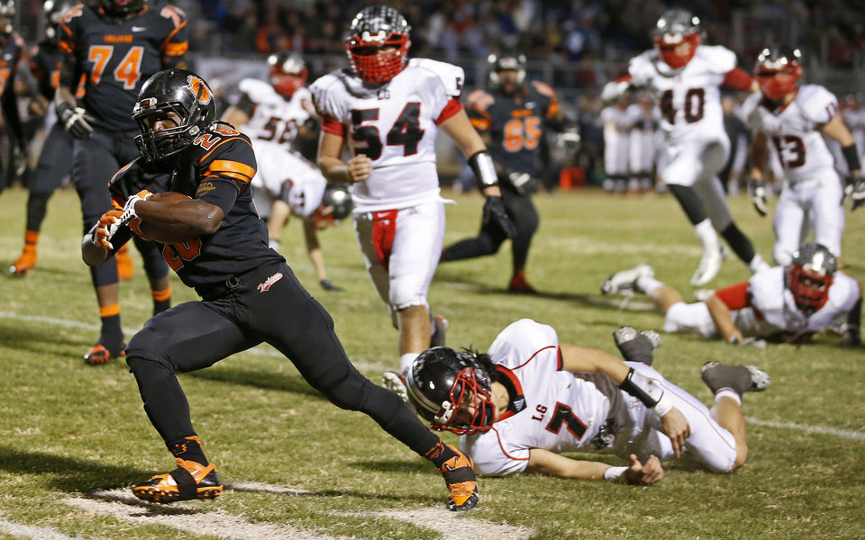 Photo - Anthony Jackson of Douglass runs past Locust Grove's Tyler Panther (7) on his way to a touchdown during their high school football playoff game at Douglass in Oklahoma City, Friday, Nov. 28, 2014. Photo by Bryan Terry, The Oklahoman