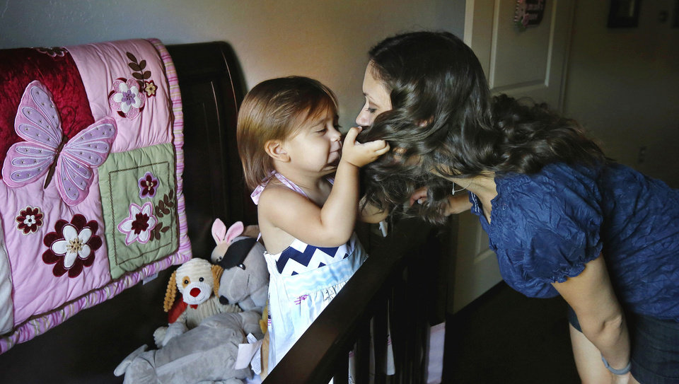 Photo - Addy Miller plays with her mother's hair after she leaned down to give her daughter a kiss before Addy takes an afternoon nap. Steve and Andrea Miller have a 2 year-old daughter, Addy.  LaDonna Woodmansee was surrogate mother for the Millers because Mrs. Miller couldn't carry the baby. They are photographed in their home in southeast Oklahoma County on Wednesday, Aug. 21, 2013. Story is about surrogacy in Oklahoma.   Photo  by Jim Beckel, The Oklahoman.
