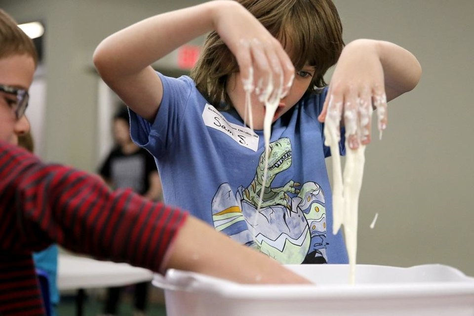 Photo - Sam Streets, 9, plays with a mixture of cornstarch and water during a day camp at the Science Museum Oklahoma in Oklahoma City, Tuesday, April 3, 2018. [Photo by Bryan Terry/The Oklahoman Archives]