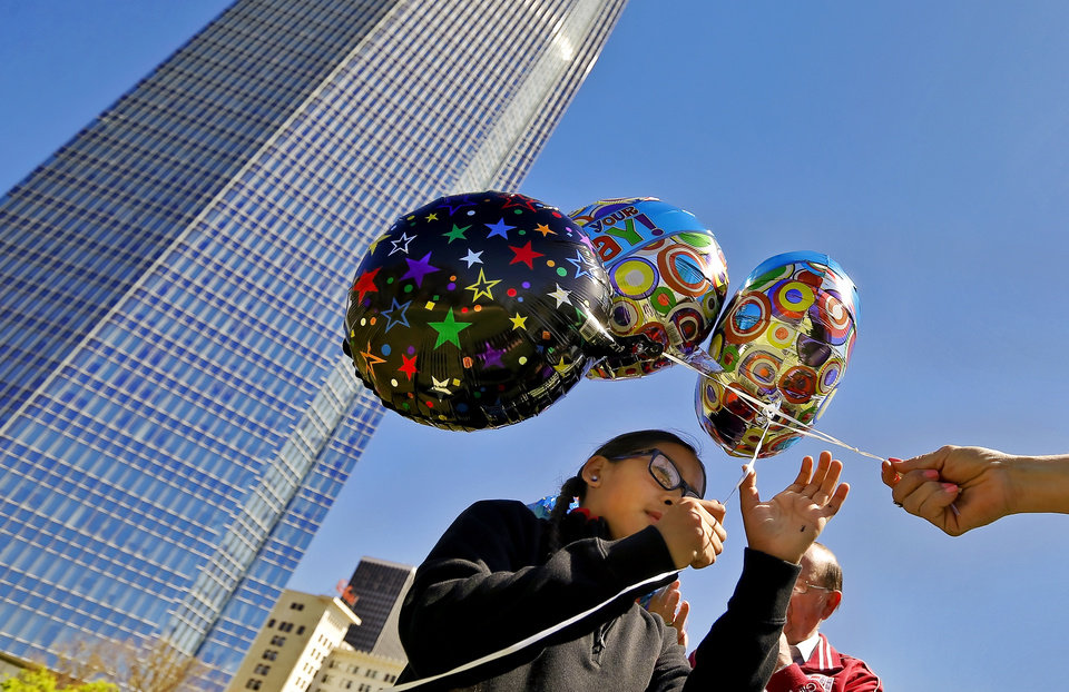 Photo - Jaylon Wahnee gathers balloons to release after family members wrote personal messages on the balloons in honor of his uncle Bradley Wahnee, who was killed in 2009 during a drive by shooting, to mark his birthday at the Myriad Botanical Gardens in Oklahoma City, Okla. on Monday, March 21, 2016. The family releases balloons every year on Bradley's birthday and the date he was killed.  Photo by Chris Landsberger, The Oklahoman