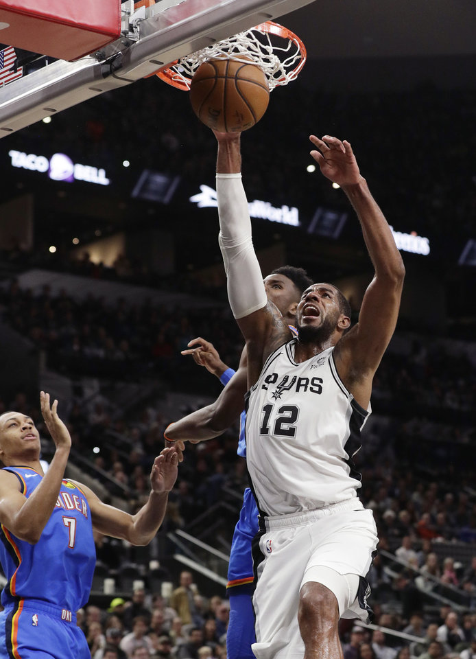 Photo - San Antonio Spurs center LaMarcus Aldridge (12) scores over Oklahoma City Thunder forward Darius Bazley (7) during the second half of an NBA basketball game, in San Antonio, Thursday, Jan. 2, 2020. Oklahoma City won 109-103. (AP Photo/Eric Gay)