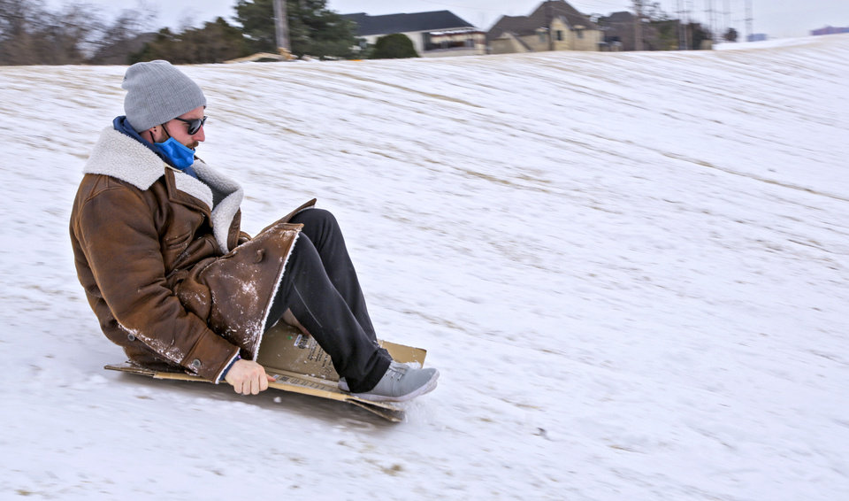 Photo - Mason uses cardboard to sled down a hill near Lake Hefner in Oklahoma City, Okla. on Tuesday, Feb. 16, 2021.  [Paige Dillard/The Oklahoman]