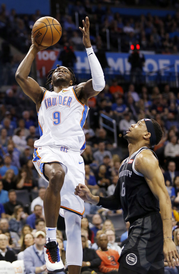 Photo - Oklahoma City's Jerami Grant (9) goes to the basket next to Detroit's Bruce Brown (6) in the first quarter during an NBA basketball game between the Detroit Pistons and the Oklahoma City Thunder at Chesapeake Energy Arena in Oklahoma City, Friday, April 5, 2019. Photo by Nate Billings, The Oklahoman