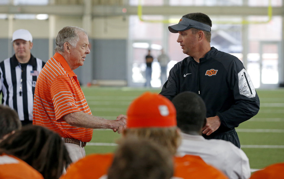 Photo - Boone Pickens, left, shakes hands with head coach Mike Gundy after Pickens spoke with the football team during a practice in Stillwater, Okla., Friday, April 10, 2015. Photo by Bryan Terry, The Oklahoman