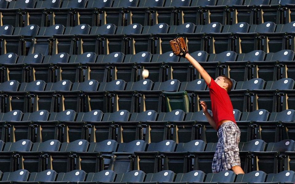 Photo -  MINOR LEAGUE BASEBALL: A fan tries to catch a foul ball during the baseball game between the Oklahoma City RedHawks and the Las Vegas 51s at the AT&T Bricktown Ballpark, Friday, Aug. 13, 2010, in Oklahoma City. Photo by Sarah Phipps, The Oklahoman       ORG XMIT: KOD