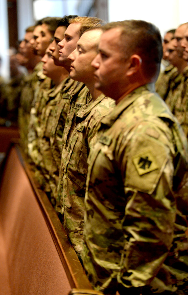 Photo -  Soldiers stand for the National Anthem during a sendoff ceremony for members of the Oklahoma National Guard's 1st Battalion, 179th Infantry Regiment at First Baptist Church of Moore. The battalion is deploying to Ukraine early next year. [Photo by Jackie Dobson, for The Oklahoman]