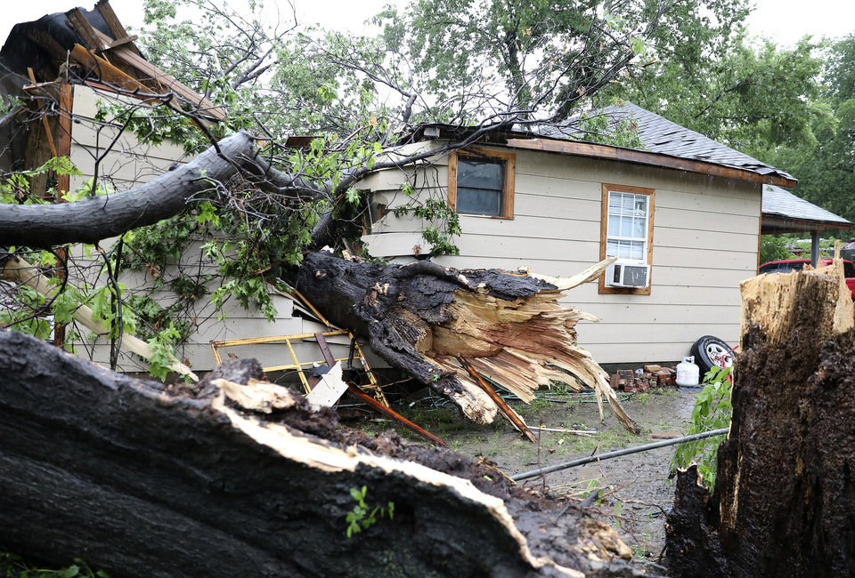 Photo - A large tree rests inside a home where a man was rescued near Newton and St. Louis Avenue in Tulsa, Okla., on Tuesday, May 21, 2019. (Tom Gilbert/Tulsa World via AP)