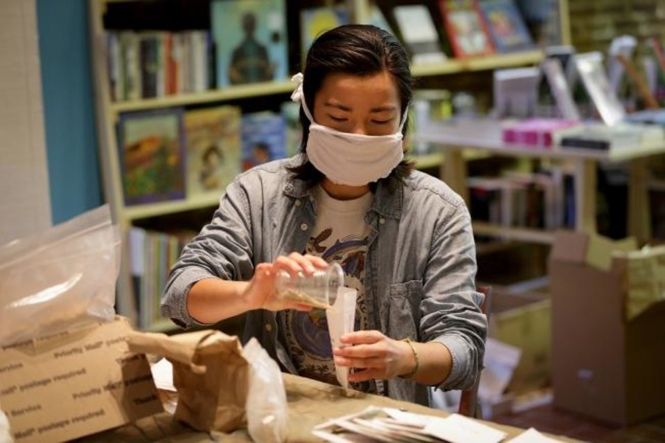 Photo -  Volunteer Shelby Kim fills an envelope with cherry tomato seeds April 22 inside the Making Worlds bookstore in Philadelphia. A group of volunteers are packing up tens of thousands of seeds to ship to gardeners around the country. [David Maialetti/The Philadelphia Inquirer/TNS]