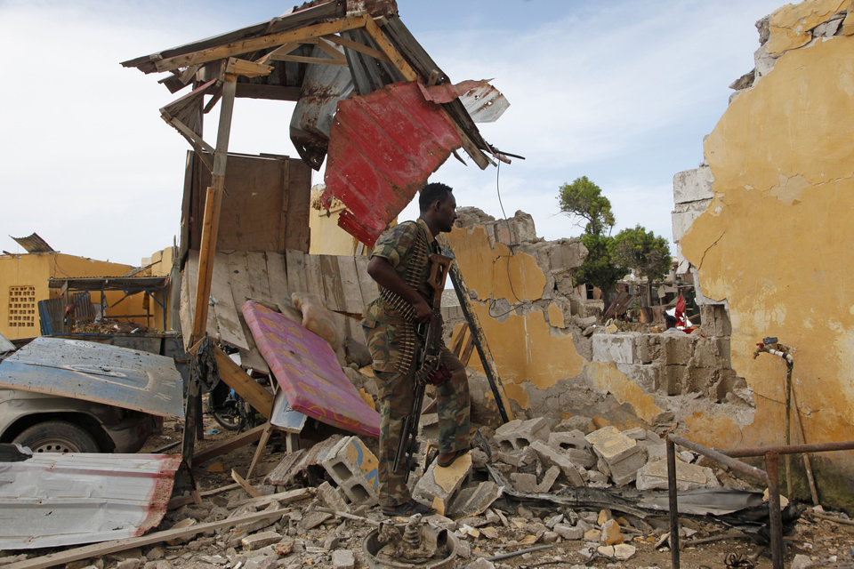 A Somali soldier stands near a destroyed building outside the police traffic station in Mogadishu, Somalia, Monday, May, 9, 2016. A Somali police official says a suicide car bomber struck the entrance of the East African country's traffic police headquarters in the capital, killing four people and injuring others. Somalia's Islamic extremist rebels, al-Shabab, claimed responsibility for the attack, which shattered a period of calm in the seaside city. (AP Photo/Farah Abdi Warsameh)