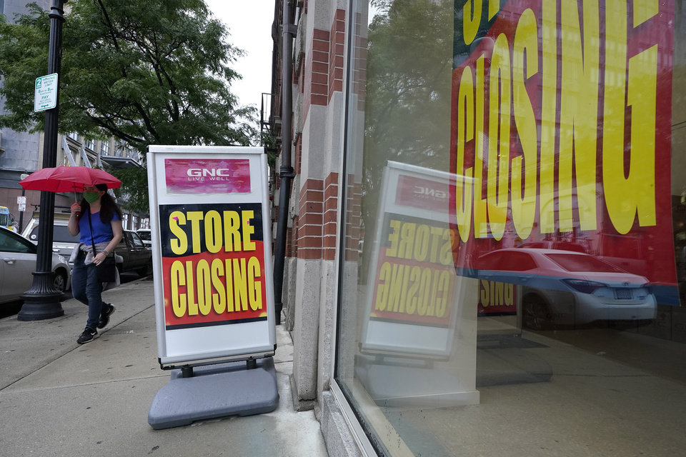 Photo -  A passer-by walks past a business storefront with store closing signs, Wednesday, Sept. 2, 2020, in Boston. The Congressional Budget Office has warned that the government this year will run the largest budget deficit, as a share of the economy, since 1945, the year World War II ended. Next year, the federal debt — made up of the year-after-year gush of annual deficits — is forecast to exceed the size of the entire American economy for the first time since 1946.   (AP Photo/Steven Senne)