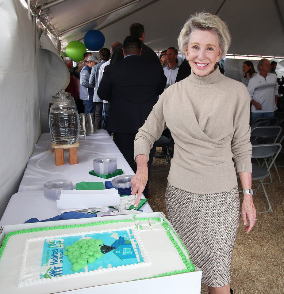 Photo - Ann Felton Gilliland cuts the cake. Habitat for Humanity's 1,000th home, Monday, March 9, 2020.  [Photo by Doug Hoke/The Oklahoman]