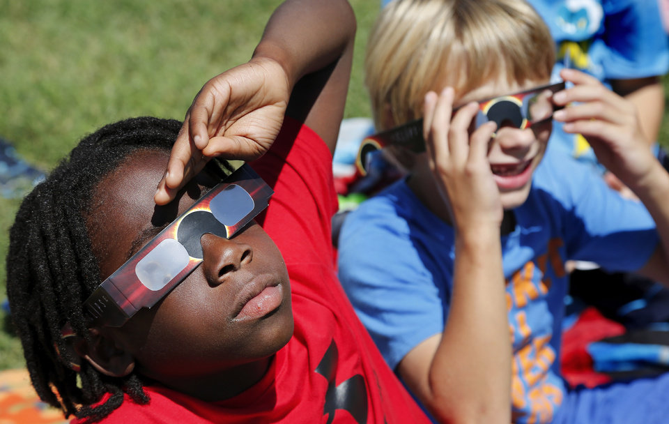 Photo - Jaylen Baskerville, third grade, and classmates look up at the sky to view the eclipse. The entire student body, faculty and some parents gathered in a field on the north side of  James Griffith Intermediate School to view the solar eclipse Monday afternoon, Aug. 21, 2017.  Special glasses with very dark lenses were purchased to allow teachers and students to safely view the celestial event. Children were served  Moon Pies as a snack to enjoy while viewing the eclipse. Photo by Jim Beckel, The Oklahoman