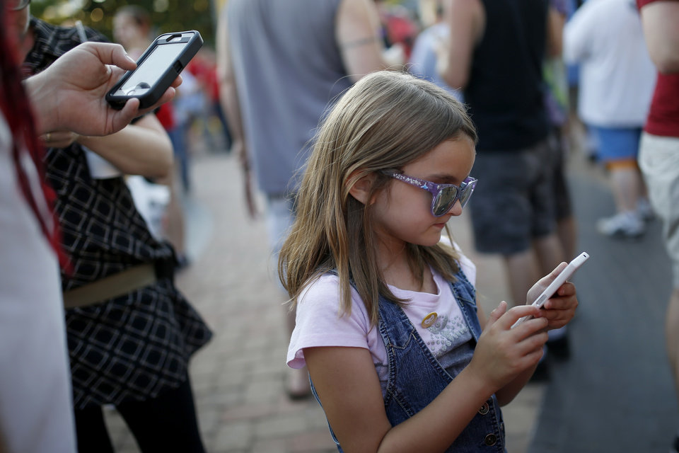 Photo - Jane Stevens, 7 1/2, plays Pokemon Go during a meetup for players of the game in Oklahoma City at Bricktown on Friday, July 29, 2016. Photo by Bryan Terry, The Oklahoman