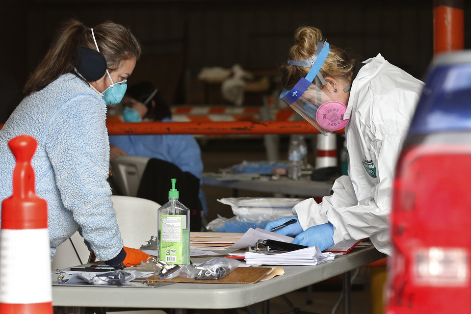 Photo - Registered nurses Geri Taylor, left, and Joni Phelps, go through paperwork at a mobile testing site for COVID_19 at the Murray County Expo Center in Sulphur, Okla., Tuesday, April 14, 2020. (AP Photo/Sue Ogrocki)