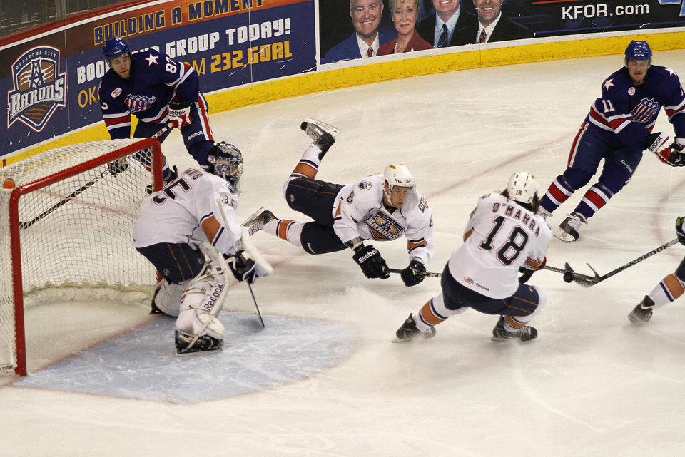 Photo - AHL HOCKEY: OKC's Dan Ringwald (6) trips while defending the home goal during a game between the Oklahoma City Barons and the Rochester Americans at the Cox Convention Center in Oklahoma City, Tuesday, Dec. 27, 2011.  Photo by Garett Fisbeck, The Oklahoman  ORG XMIT: KOD