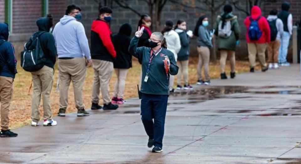 Photo -  A school official announces instructions as students wait in line to return to class at U.S. Grant High School in Oklahoma City, Okla. on Tuesday, Nov. 10, 2020. Students in grades first through 12th return to Oklahoma City Public Schools for the first time since March. The school district will have students attend in-person classes twice a week in a hybrid A/B schedule. [Chris Landsberger/The Oklahoman]