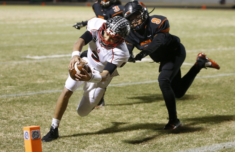 Photo - Locust Grove's Mason Fine dives in for a touchdown in front of Douglass' Terrance Bagby during their high school football playoff game at Douglass in Oklahoma City, Friday, Nov. 28, 2014. Photo by Bryan Terry, The Oklahoman