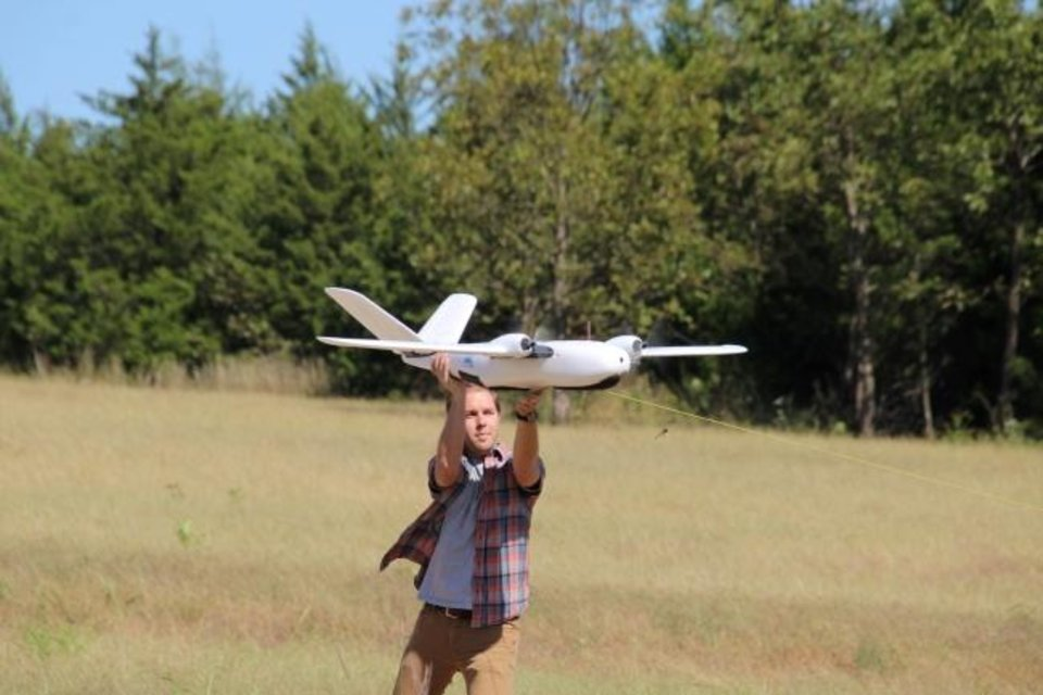 Photo -  An Oklahoma State University researcher helps launch a drone for a Vigilant Aerospace Systems flight test. Vigilant is developing software that will allow drones to fly and navigate autonomously. [JAMEY JACOB/OKLAHOMA STATE UNIVERSITY]