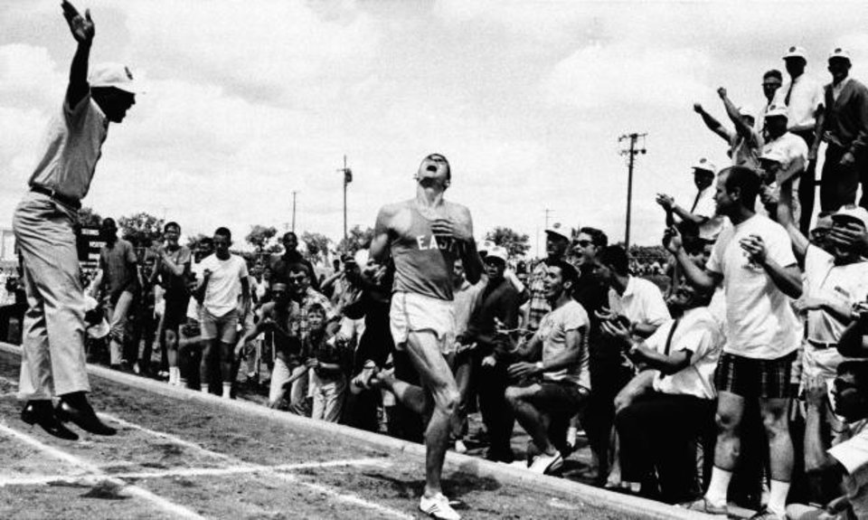 Photo -  Jim Ryun crosses the finish line after running one mile in 3 minutes, 58.3 seconds at a Kansas high school track meet in 1965, setting a national record. [AP FILE PHOTO]