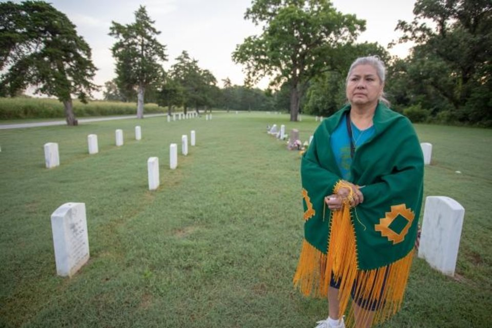Photo -  Penny Soontay, a member of the Apache Tribe, and the United Methodist Church of Apache, stands in an Apache POW cemetery at Fort Sill during a prayer vigil. [Ginny Underwood/Oklahoma Indian Missionary Conference]