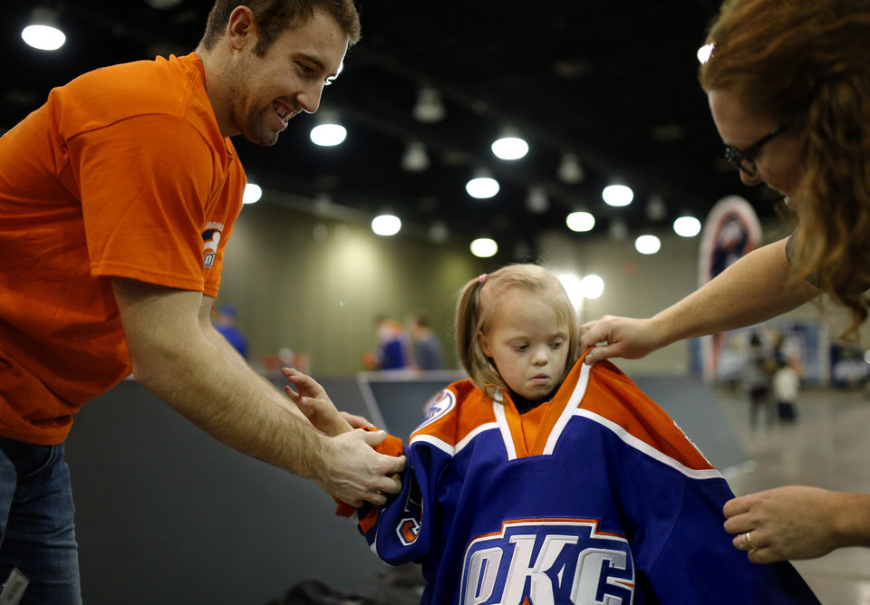 Photo - Mia Dickinson ,6, receives help from her Barons Buddy Brad Hunt and her mother Meghan Dickinson as she puts on Hunt's jersey during a Barons Buddies event with the Oklahoma City Barons and Special Olympians in Oklahoma City, Tuesday, November 5, 2013. The Special Olympians and their families were introduced to the Barons player that they will paired with throughout the year. Photo by Bryan Terry, The Oklahoman