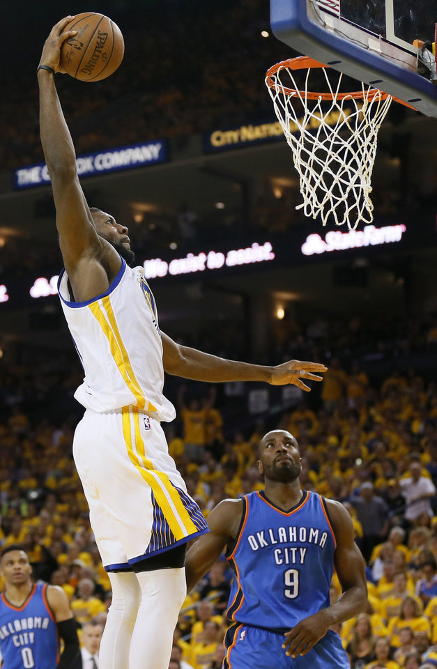 Photo - Golden State's Festus Ezeli (31) dunks the ball in front of Oklahoma City's Serge Ibaka (9) during Game 2 of the Western Conference finals in the NBA playoffs between the Oklahoma City Thunder and the Golden State Warriors at Oracle Arena in Oakland, Calif., Wednesday, May 18, 2016. Golden State won 118-91. Photo by Nate Billings, The Oklahoman
