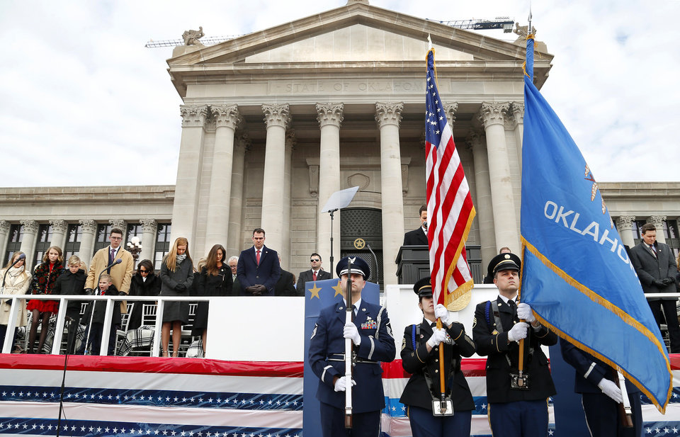 Photo - Gov. Kevin Stitt with his wife, Sarah, and their six children, on the platform with other elected officials and dignitaries during the invocation and posting of the colors at the beginning of the inauguration ceremony where he was sworn in as Oklahoma's 28th governor by Supreme Court Chief Justice Noma Gurich on Monday, Jan. 14, 2019. Photo by Jim Beckel, The Oklahoman.