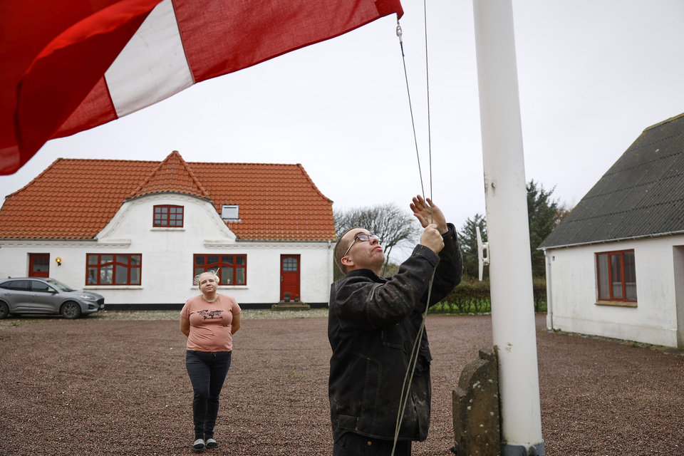 Photo -  Peter and Trine Brinkmann Nielsen put their flag to halfmast at the Norden mink farm, after the government called for the culling of minks, in Boerglum Kloster, Denmark. Thursday, Nov. 5,  2020.  Denmark's prime minister says the government wants to cull all 15 million minks in Danish farms, to minimize the risk of them re-transmitting the new coronavirus to humans. She said Wednesday, Nov. 4, 2020, a report from a government agency that maps the coronavirus in Denmark has shown a mutation in the virus found in 12 people in the northern part of the country who got infected by minks. (Claus Bjoern Larsen/Ritzau Scanpix via AP)