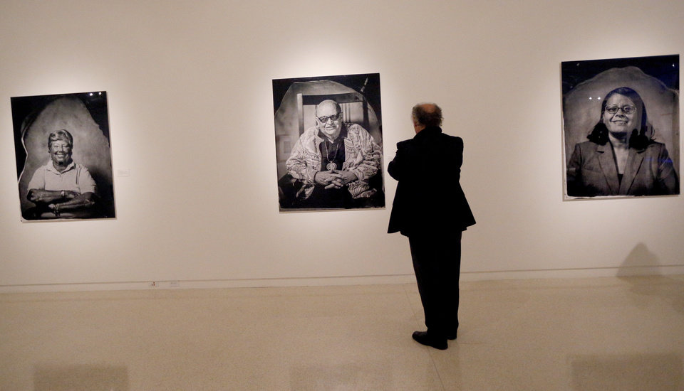 Photo -  Richard Zielinski looks at Will Wilson's Photo/synthesis exhibition of tintypes of American Indians at the Fred Jones Jr. Museum of Art. The exhibition was funded through a grant from the National Endowment for the Arts. Some in Oklahoma's arts community worry about the fate of that agency under the Trump administration. Photo by Sarah Phipps, The Oklahoman
