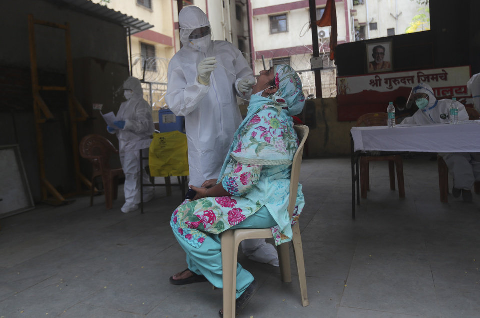 Photo -  A health worker takes a swab test of a woman during a free medical checkup in Dharavi, one of Asia's biggest slums, in Mumbai, India, Friday, June 26, 2020. India is the fourth hardest-hit country by the pandemic in the world after the U.S., Russia and Brazil. (AP Photo/Rafiq Maqbool)