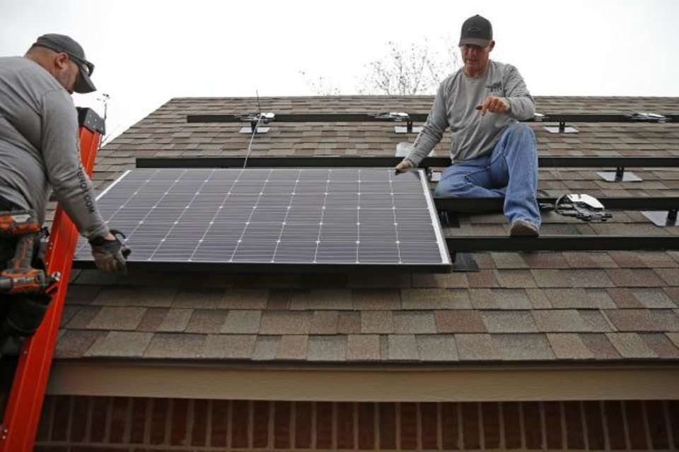 Photo -  Alex Lopez and Jeremy Rains, with Solar Power of Oklahoma, install solar panels on an Edmond home. [BRYAN TERRY/THE OKLAHOMAN]