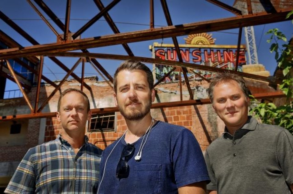 Photo -  Ben Sellers, Jonathan Dodson and David Wanzer, from left, pose for a photo in the long-abandoned Sunshine Cleaners building on NW 1 and Classen in 2015 prior to restoring it into a brewery and offices. [CHRIS LANDSBERGER/THE OKLAHOMAN ARCHIVES]