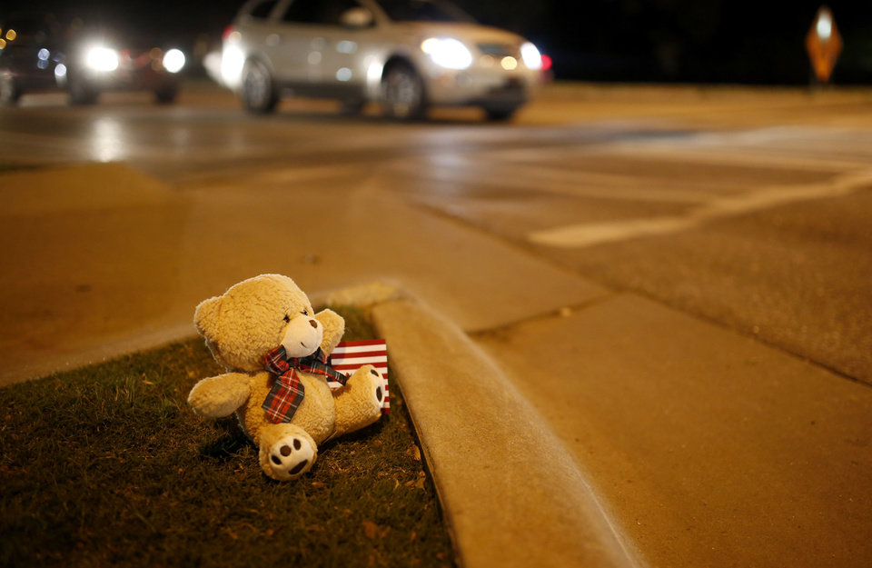 Photo - A teddy bear sits on the corner of Main and Hall of Fame where earlier a car crashed into spectators during the Oklahoma State University homecoming parade killing 4 people and injured several in Stillwater, Okla., Saturday, Oct. 24, 2015. Photo by Sarah Phipps, The Oklahoman
