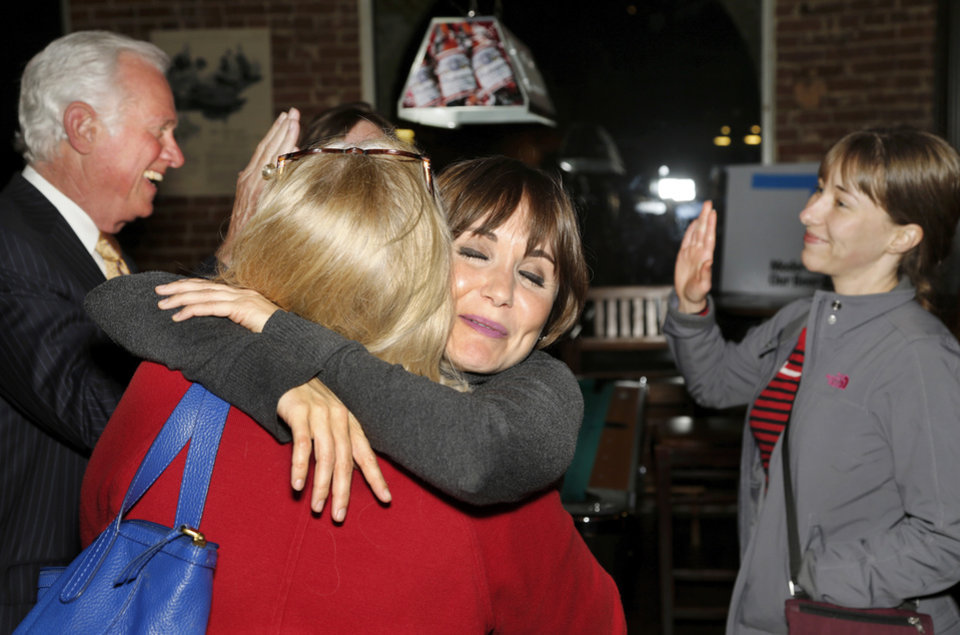 Photo -  Sunny Cearley, facing camera, hugs a woman after it was clear that State Question 792 was going to pass. In background, Roy Williams, left, exchanges high-fives with another supporter. Williams is president and CEO of Greater Oklahoma City Chamber. Supporters of SQ 792 gathered at an election watch party at Bricktown Brewery. [Photo by Jim Beckel, The Oklahoman]