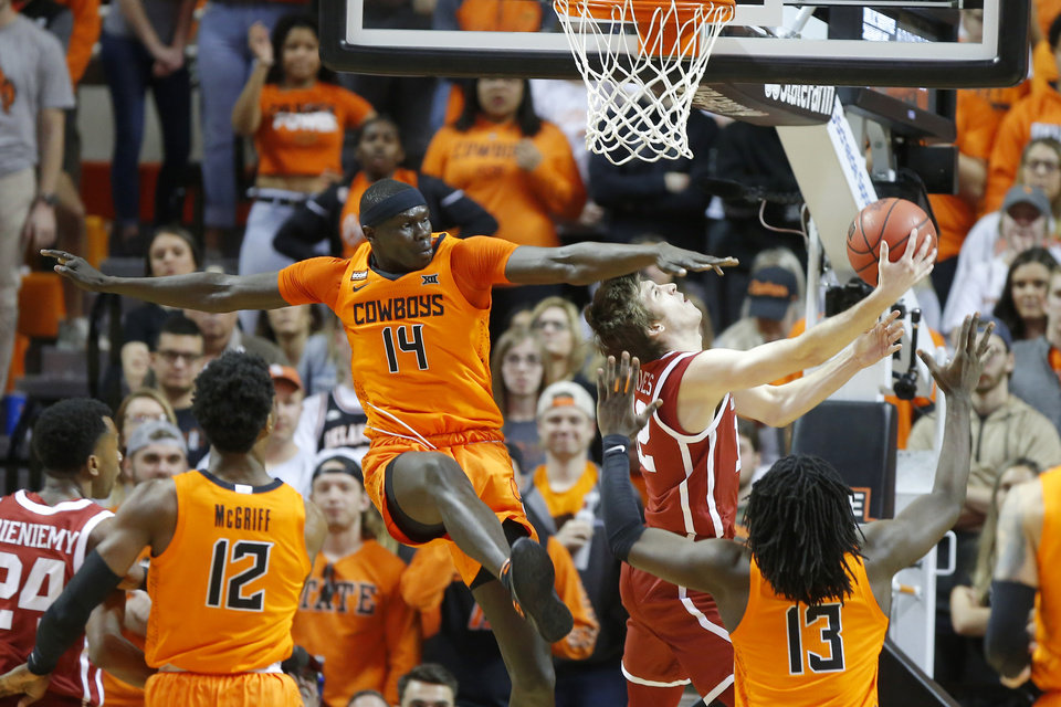 Photo - Oklahoma State's Yor Anei (14) fouls Oklahoma's Austin Reaves (12) during an NCAA men's Bedlam basketball game between the Oklahoma State University Cowboys (OSU) and the University of Oklahoma Sooners (OU) at Gallagher-Iba Arena in Stillwater, Okla., Saturday, Feb. 22, 2020. [Bryan Terry/The Oklahoman]