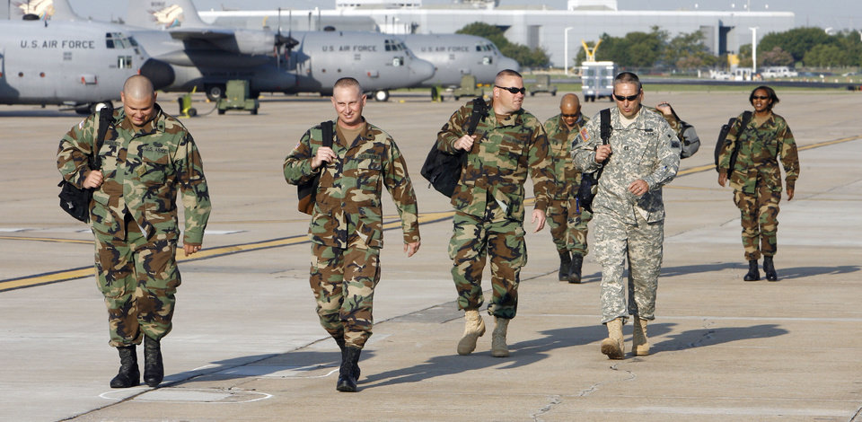 Photo - ILLEGAL IMMIGRATION, IMMIGRANTS: Oklahoma Army National Guard members of the 120th Combat Engineers unit walk onto the flight line at a Guard hanger at Will Rogers World Airport in Oklahoma City Thursday Sept. 7, 2006, to board a national guard plane bound for Las Cruces, New Mexico, to participate in Operation Jump Start to better secure the nation's border with Mexico. 13 engineers from the unit flew out Thursday to participate in the operation. BY PAUL B. SOUTHERLAND, THE OKLAHOMAN ORG XMIT: KOD