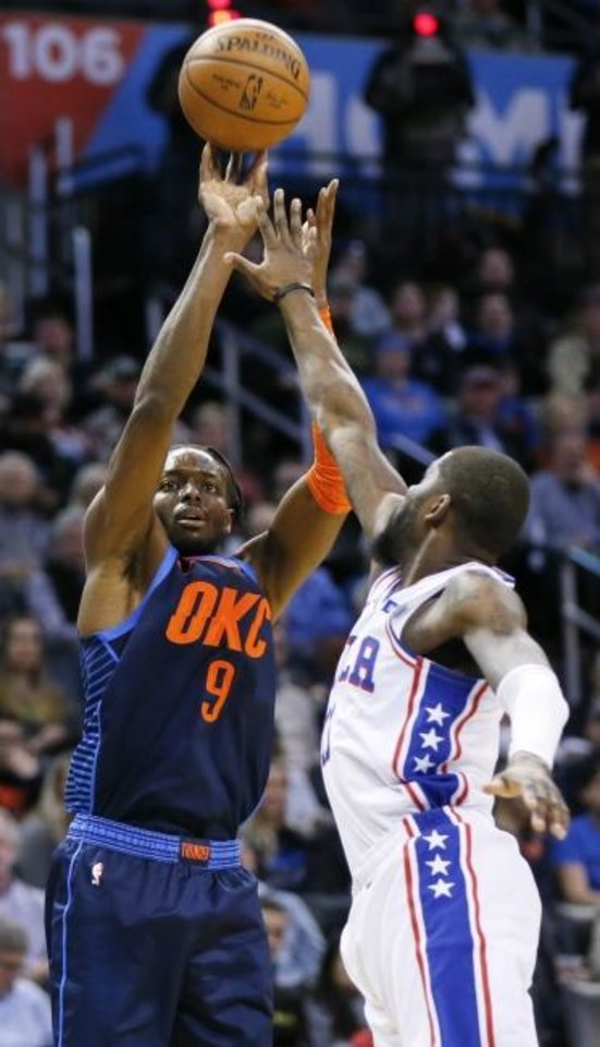Photo -  Oklahoma City's Jerami Grant, left, shoots over Philadelphia's James Ennis III  in the first quarter of Thursday night's game at Chesapeake Energy Arena. [Nate Billings/The Oklahoman]