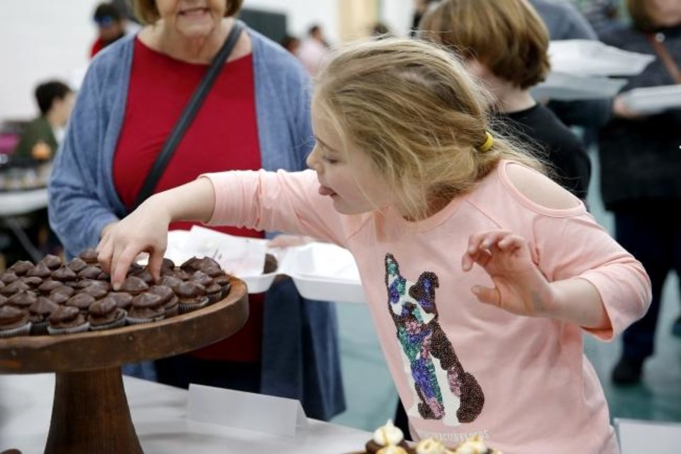Photo -  Allison Lassetter, 7, selects a chocolate treat Saturday.  [Bryan Terry/The Oklahoman]
