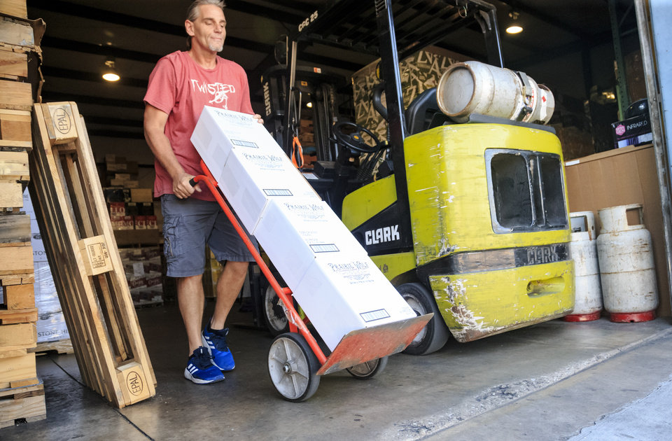 Photo - Gregory Gourley, of Premium Brands Wines and Spirits, loads a truck with liquor at the company's warehouse in Oklahoma City, Okla. on Wednesday, Sept. 19, 2018. Photo by Chris Landsberger, The Oklahoman