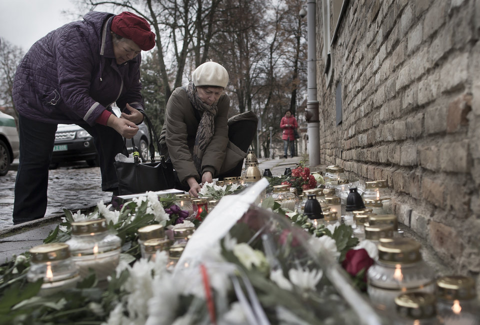 Photo - People light candles outside the French embassy in Vilnius, Lithuania, Saturday, Nov. 14, 2015, for the victims killed in Friday's attacks in Paris. French President Francois Hollande said more than 120 people died Friday night in shootings at Paris cafes, suicide bombings near France's national stadium and a hostage-taking slaughter inside a concert hall.  (AP Photo/Mindaugas Kulbis)