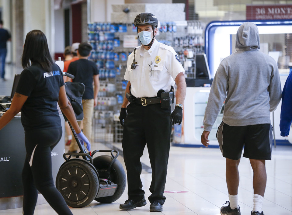 Photo - A security guard wears a mask at Penn Square Mall during the re-opening of the mall after being closed because of the coronavirus pandemic, in Oklahoma City, Friday, May 1, 2020. [Nate Billings/The Oklahoman]